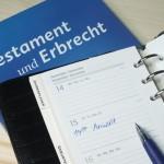 """Blaues Buch mit der Aufschrift """"Testament und Erbrecht"""". Darüber liegt ein Terminplaner mit dem Eintrag """"Anwalt um 14:00 Uhr"""" am Dienstag."""