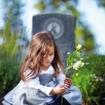 Ein kleines Mädchen sitzt vor dem Grab mit einer weißen Rose in der Hand.