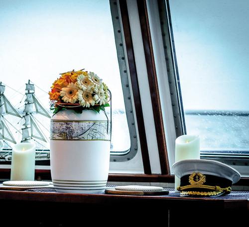 Seebestattung: geschmückte Urne im maritimen Design für die feierliche Zeremonie auf einem Schiff mit Trauerfeier und Bestattung